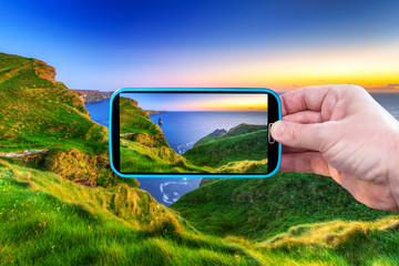 Wall Mural - Making photos by smartphone of irish cliffs at sunset