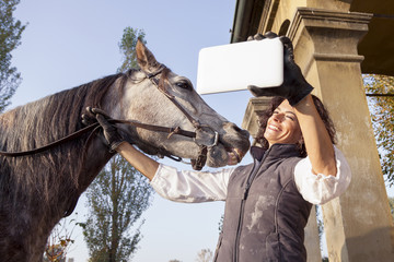 horsewoman takes a selfie with his horse to the country roads in