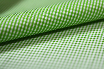 close up roll green and white scott pattern fabric of shirt