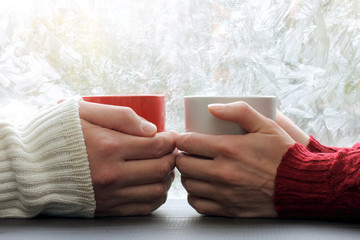 share warmest feelings/ warming meeting couple in love pair on a background of frozen window with a winter pattern