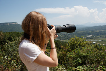 Young woman taking landscape photo with professional camera with telephoto lens