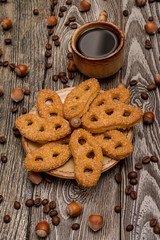 Small cups of coffee, cookies, cocoa beans and hazelnuts on wooden background