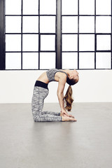 Flexible young woman in yoga position, studio