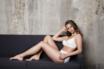 Stunning sexy woman in lingerie on sofa