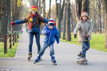 Three kids learning to ride in autumn park on rollerblades