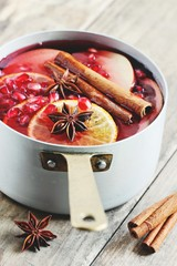 Mulled wine,punch,bowle oder sangria : winter traditional warming drinks with spicy,citrus fruits and pomegranate . Rustic style.Selective focus