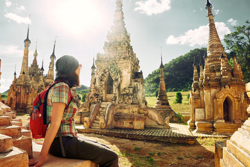 Traveller with backpack resting and looks at Buddhist stupas.