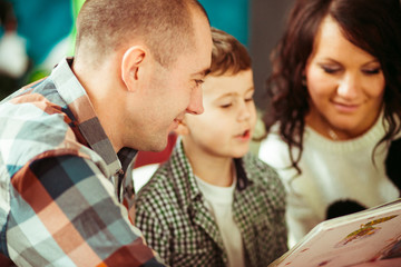 Man in plaid shirt reads book with his woman and son