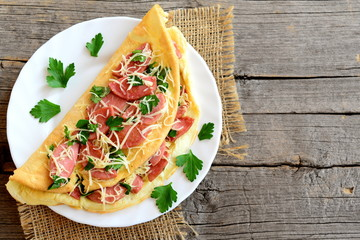 Delicious sausage and cheese omelette on a plate and an old wooden background with blank copy space for text. Eggs omelette with a filling. Vintage style. Top view