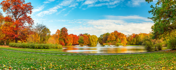 Beautiful fall landscape and cloudy sky. Autumn panorama - yellowed trees in city park in cloudy weather. Pond with fountains in South Park, Wroclaw Poland.