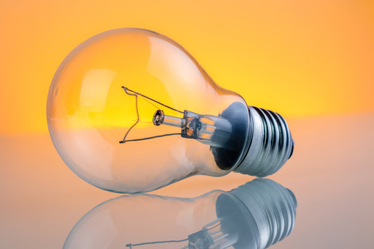retro vintage light bulb with on warm light yellow tint background