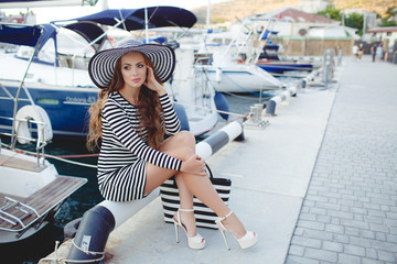 Beautiful young  woman with long curly hair on his head wearing a striped straw hat with a large brim,clad in a striped summer dress,spends time on the ocean,close to Parking of boats and yachts