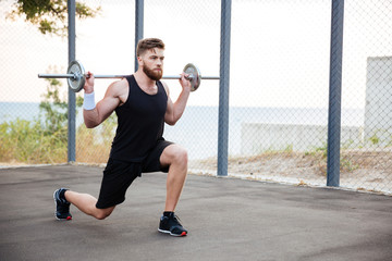 Concentrated young bearded sports man doing squatting exercises with barbell