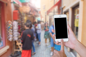 Hands woman are holding touch screen smart phone,tablet on blurred people shopping on street markets old building style background.