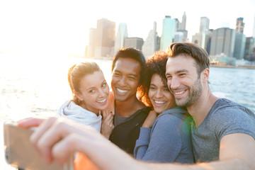 Friends taking selfie picture on Brooklyn heights promenade, NYC