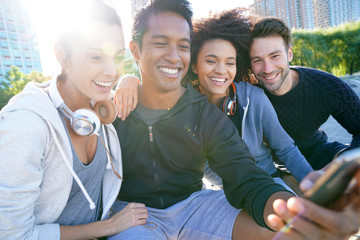 Group of friends in casual outfit taking selfie picture with smartphone