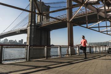 USA, New York City, man skipping rope at East River under Brooklyn Bridge