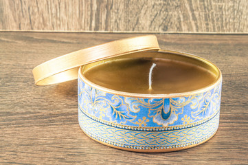 Handmade candle made in the golden rounded box decorated with textured fabric. Scenery and wooden background.