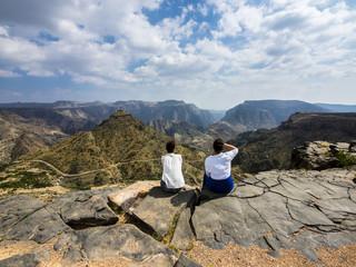 Two women looking at mountain view, Jabal Akhdar, Oman