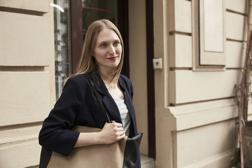 Smiling woman with bag outdoors