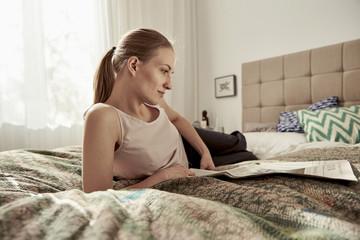Woman reading newspaper in bedroom
