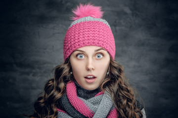 Surprised young woman in winter hat and scarf.