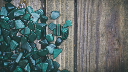 Malachite on wooden background, small shells on a wooden backgro