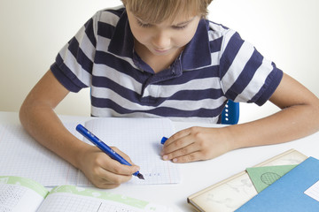 Little kid writing on notebook while doing homework at home. Close up