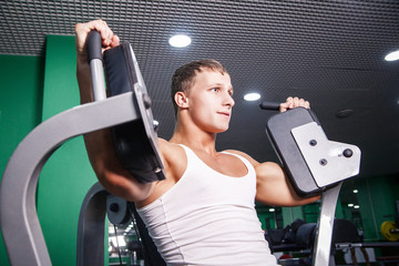 Athlete doing chest exercise on machine in gym