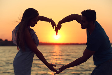 Young couple in love holding hands in the shape of a large heart on the beach at sunset