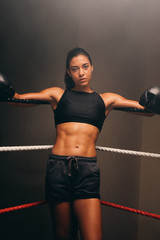 Young female boxer wears gloves and black shorts