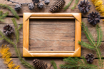 Christmas tree branches and cones with space for text in a wooden photo frame