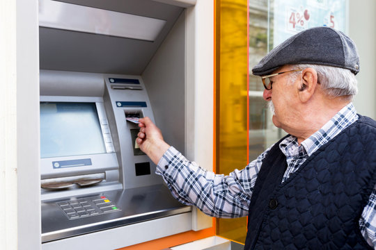elderly man inserting credit card to ATM
