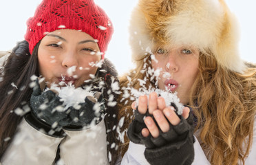 Two attractive women blowing snow in winter