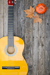 winter music symbol with autumn leaves and guitar on old wooden plank