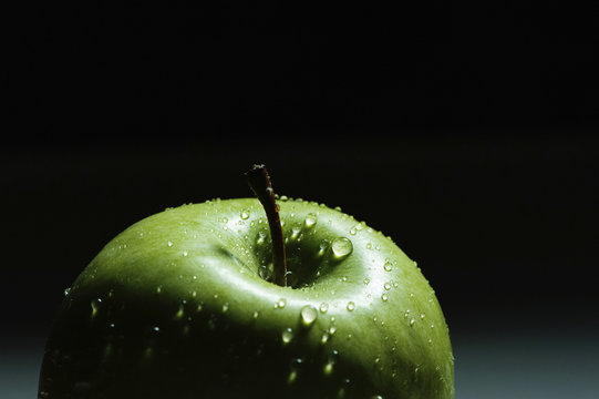 Close-up of wet green apple against black background