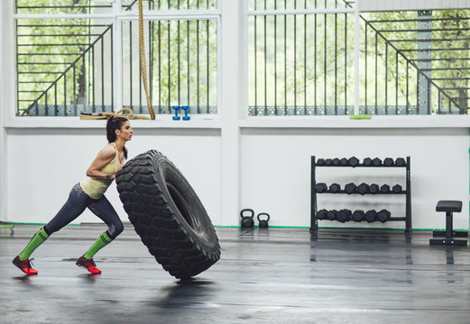 Athlete exercising with tractor tire in gym