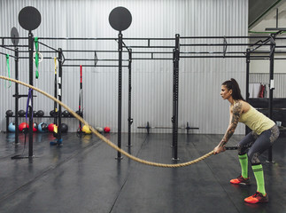 Woman doing battle rope exercise in gym
