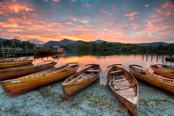Wall Mural - Stunning sunset over wooden rowing boats on Derwentwater at Keswick in the Lake District Nationla Park in Cumbria