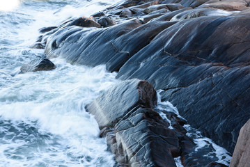 Rolling wave slamming on the rocks of the Finnish coastline