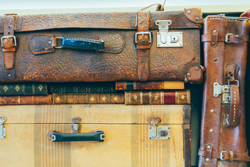 Antique suitcases stacked with old books