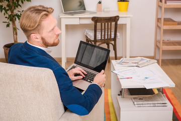 Image of confident and executive European businessman sitting on sofa or couch with laptop compuer and looking away at home.