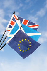 Scottish, UK, and EU flags flying together in bright blue sky