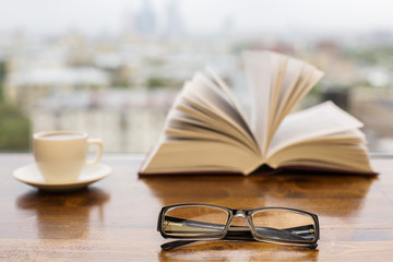 Glasses, coffee cup and open book