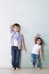 little boy and girl measuring thir height