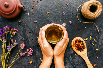 Woman's hands holding cup of tea on black background with rustic dried flowers, herbs. Top view, Flat lay.