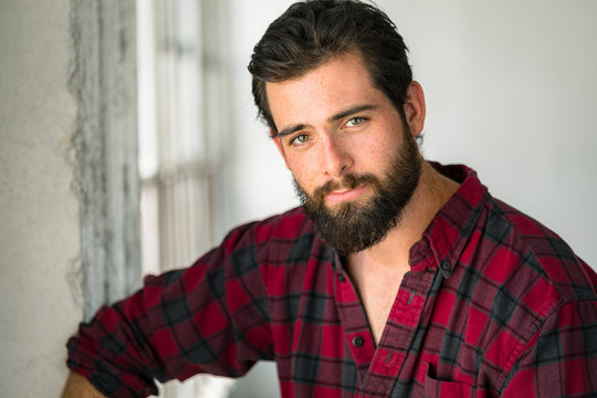 Head shot portrait of an easy going casual man with beard flannel mellow lovable gentle