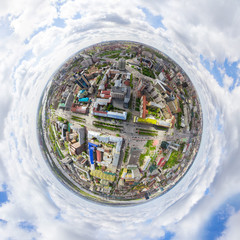 Aerial city view with crossroads and roads, houses, buildings, parks and parking lots, bridges. Copter shot. Little planet mode. Full sphere.