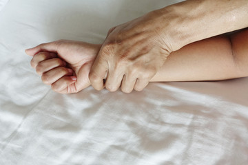 A hairy man's hand holding a woman hand for rape and sexual abus