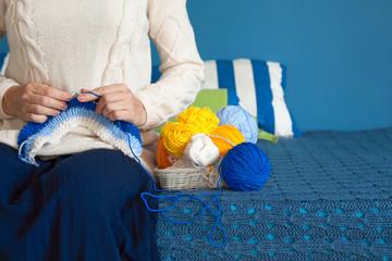 Woman in dark blue dress knit fabric of wool yarn.